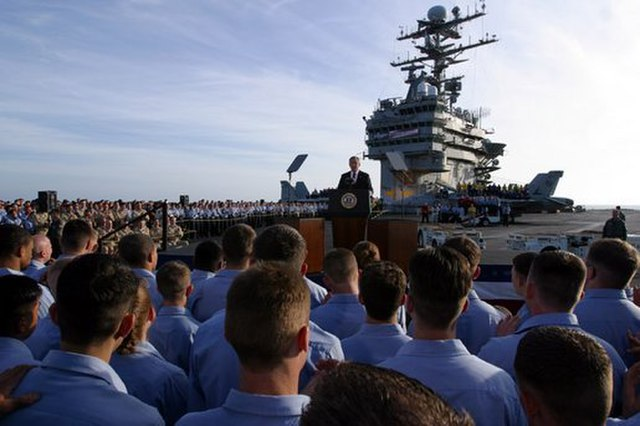 Former President George W. Bush addresses sailors and the nation from the flight deck of the USS Abraham Lincoln off the coast of San Diego, California May 1, 2003. Columnist Nathaniel Langley argues that Bush's mistakes highly outweigh his administration's accomplishments.