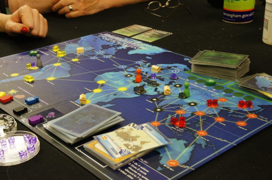 "The board game ""Pandemic"" sits on a table surrounded by multiple players. Columnist Samuel Rahman argues that people should consider buying the game to keep busy in the midst of the pandemic."