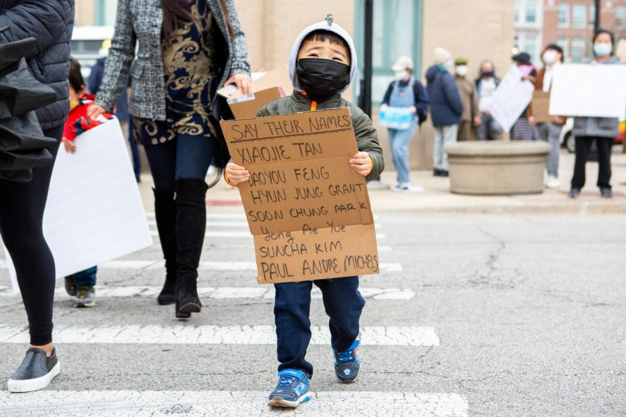 A little boy walks across North Walnut Street at the #StopAsianHate rally on March 30.