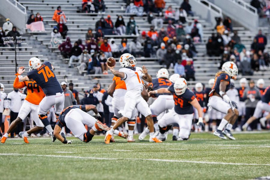 Redshirt freshman Isaiah Williams (white) throws a pass during the Orange and Blue Spring Game Monday night at Memorial Stadium. Williams and senior Brandon Peters continue to compete for the starting quarterback spot.