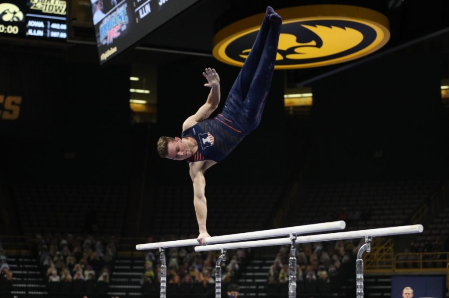 Junior Michael Fletcher performs a routine on the parallel bars against Iowa on Feb. 13. The Illinois men