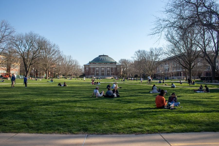 Students sit on the Main Quad overlooking Foellinger auditorium on April 3. University staff and students anticipate an enjoyable fall semester.