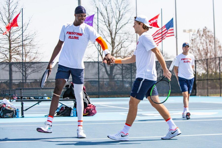 Junior Kweisi Kenyatte and senior Aleks Kovacevic high five each other after winning a point in their doubles match against Minnesota on April 4 at Atkins Tennis Center. The Illini men's tennis team were named Big Ten West division champions after a successful weekend in Iowa and Nebraska.
