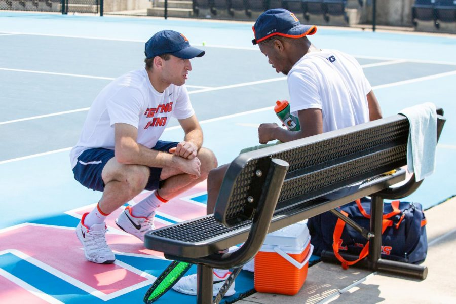 Senior Vuc Budic talks to Siphosothando Montsi in between points against Minnesota on April 4. The Illinois men's tennis team will close out their regular season at Indiana this weekend.