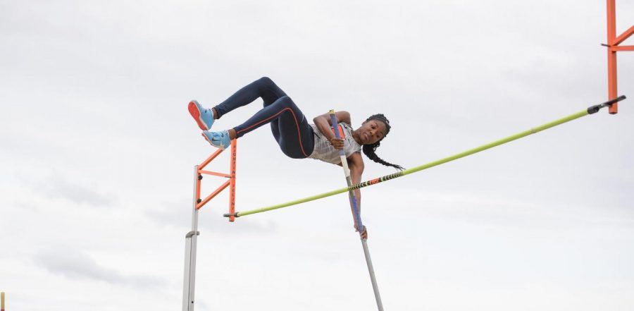 Graduate student Chisom Nwoko uses a pole to hoist herself over a bar during the pole jump event on a cloudy day. The Illinois track & field team took home multiple first place wins at the second Big Ten Invitational in Bloomington, Indiana yesterday.