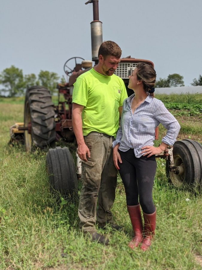Ben and Molly Oberg pose for a photo in front of a tractor on their farm in Villa Grove, Illinois.