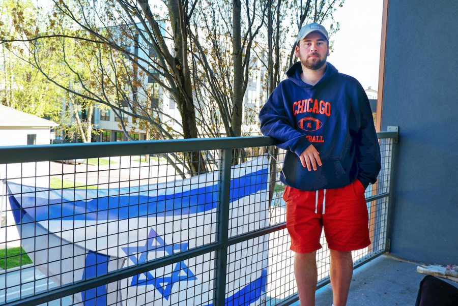 Jeremy Zelner, senior in LAS, poses for a photo on his balcony in front of his Israeli flag on April 14. Zelner is one of the many victims on campus to have experienced anti-Semitism.