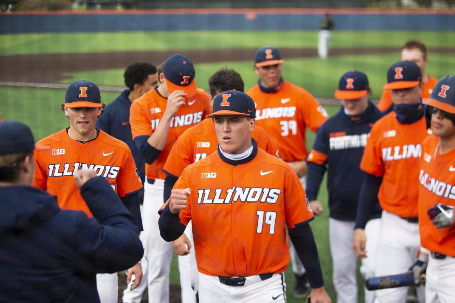 Sophomore Ryan Kutt is met by his teammates after an inning of pitching at a game against Purdue on Sunday. The Illini and the Boilermakers both won two games at this weekend's series at Illinois Field.