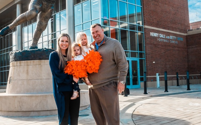 Illinois head football coach Bret Bielema and his wife Jen Bielema pose for a photo with their daughters Briella and Brexli in front of the Henry Dale and Betty Smith Football Center on Dec. 12. The Bielema family hopes to reside in Champaign for a long time.