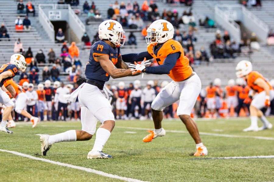 Senior Tony Adams (orange) defends sophomore Dalevon Campbell (blue) during the Orange and Blue spring game Monday night at Memorial Stadium. The Orange team won 65-15, though the score is not the biggest or most important takeaway from the game.