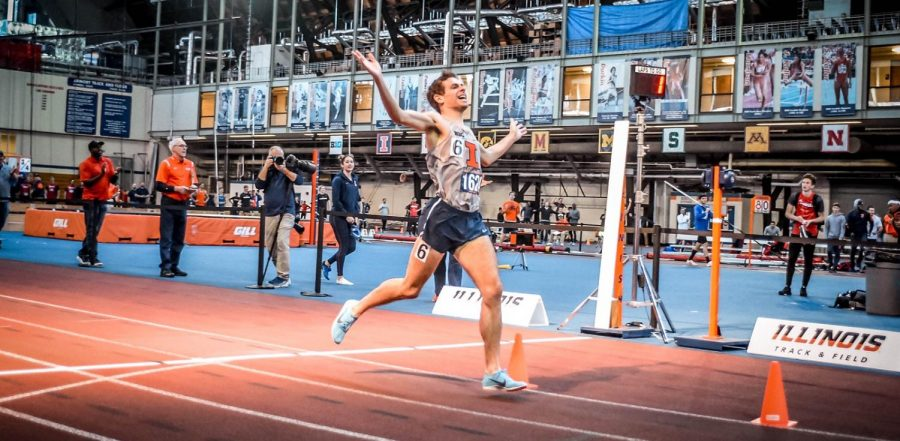 Redshirt senior Jon Davis crosses the finish line with arms raised in the Armory. The Illinois track and field team will compete at Demirjian Park this weekend for the first time.