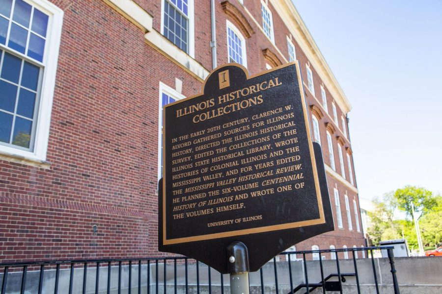 A historical marker displaying information about Illinois Historical Collections sits next to the Main Library. The University's Libraries are home to numerous historic collections and documents.