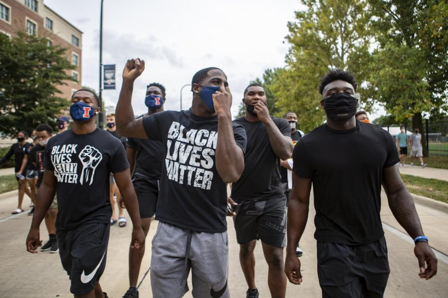 Illini football players Delano Ware, Moses Okpala, Jartavius Martin, Owen Carney, and Khalan Tolson march down First Street to protest police brutality in the black community on Aug. 31.