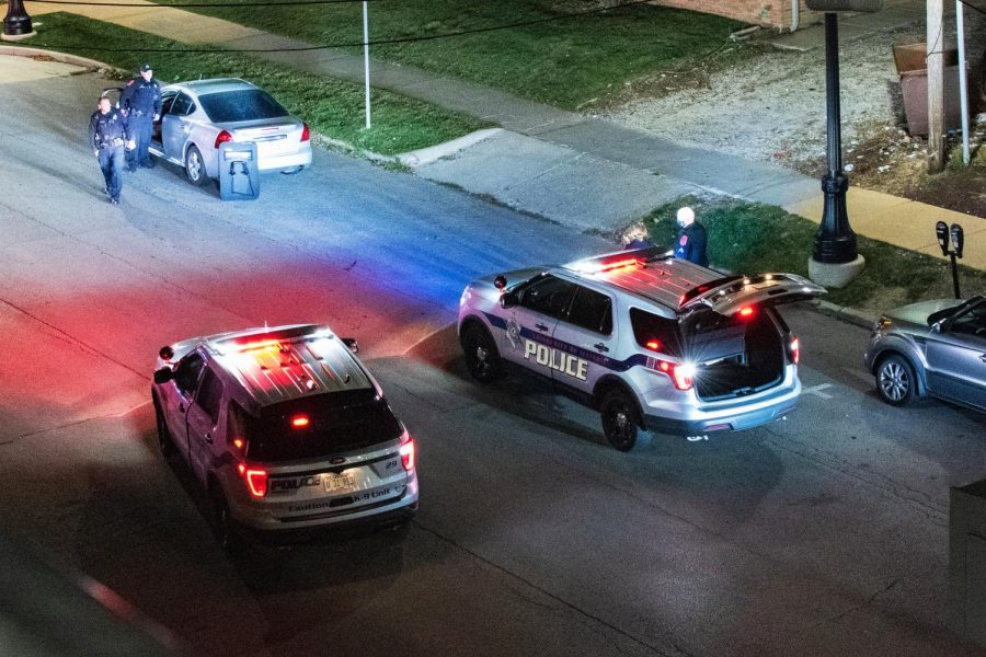 Two University police cars and multiple police officers survey campus streets on Sept. 29.