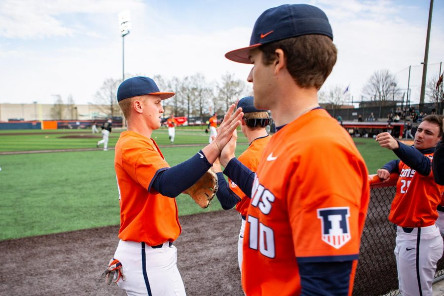 Senior Jackson Raper high fives Tom Jurack after coming off the field during the game against Purdue April 18. The Illinois baseball team is set to play at Illinois Field against Maryland this weekend after seven away games.