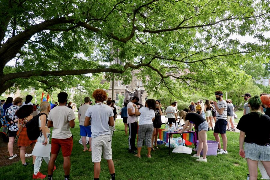 A large crowd of people congregate in front of Alma Mater passing out transgender flags and stickers on Saturday. University students protested the use of deadnames during the most recent commencement ceremony.