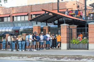 A group of students stand huddled in line outside of Joe's Brewery on Sept. 17. Effective Friday, Champaign's bars and restaurants will be able to allow customers to stand and walk around.