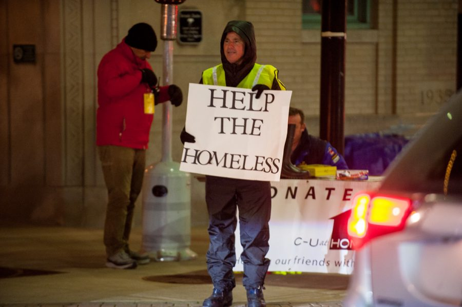 A man holds up a sign during the One Night event with C-U at Home. C-U at Home is temporarily closing due to staff shortage.