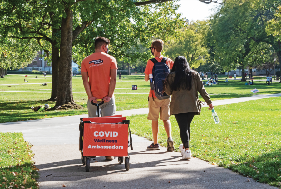 COVID-19 Wellness Ambassadors walk along the Main Quad on Oct. 7. The Daily Illini reviews influential COVID-19 moments throughout the past year.