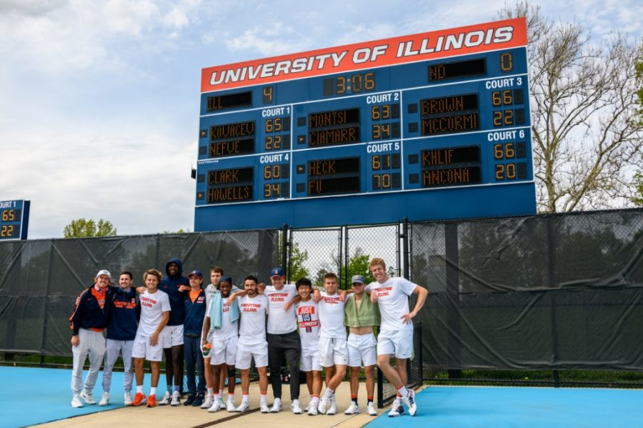 The Illinois men's tennis team poses in front of the scoreboard at Khan Outdoor Tennis Complex on Saturday. Illinois beat DePaul and Notre Dame to advance to the Sweet 16 of the NCAA tournament.