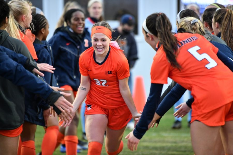 Freshman Kennedy Berschel runs through a tunnel of teammates before the game against Iowa April 8. Illinois soccer released its 2021 fall schedule featuring non-conference and of course conference games reminiscent of seasons played prior to the pandemic.