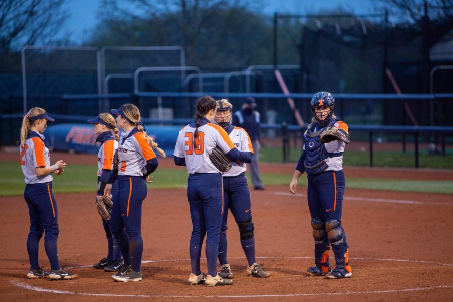 The Illinois softball team meets on the mound to discuss pitching strategies against Indiana April 23. This upcoming weekend, the Illini will face Iowa in its last four-game series of the regular season.
