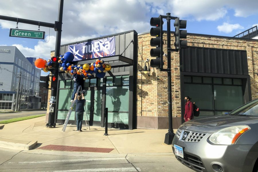 Workers at the NuEra cannabis dispensary hang balloons above the entrance April 15. The adult-use dispensary opened on Green Street last month.