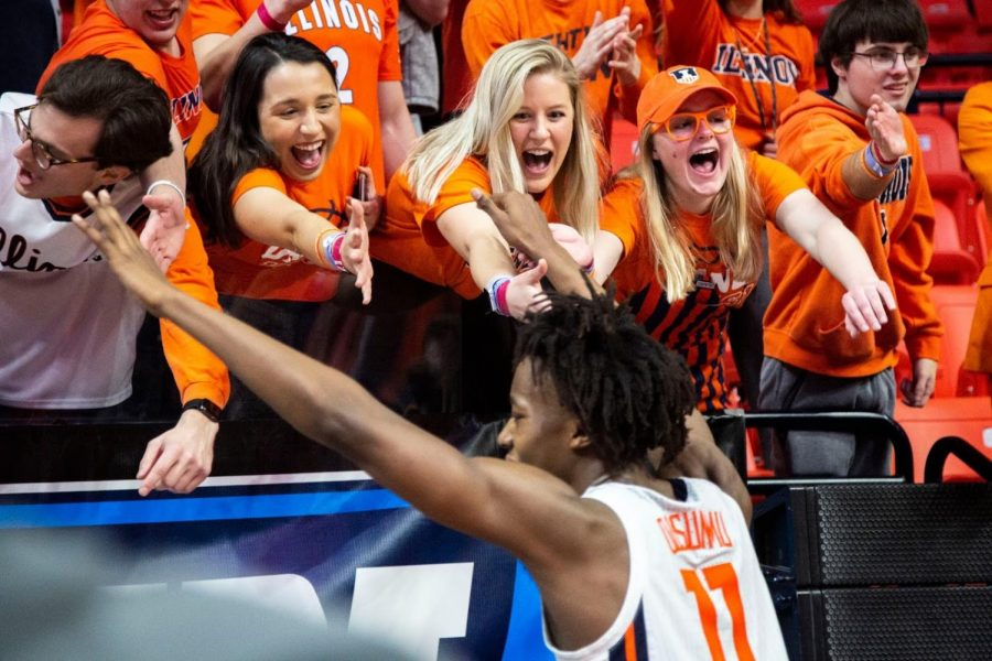 Students in the Orange Krush section of the State Farm Center lean over a railing to high five Ayo Dosunmu after Illinois won against Iowa March 8, 2020. Attending sporting events is the ideal way for passionate Illinois fans to experience campus.