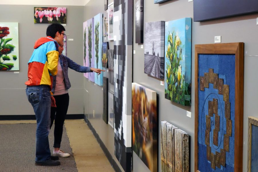 Visitors view art on display at the 2019 Boneyard Arts Festival. This year's festival will take place in-person June 18-20.