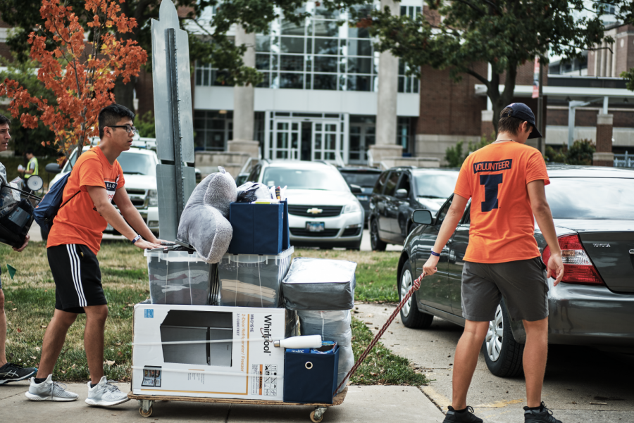 Two student move-in volunteers help transfer a roller of supplies into a dorm on Aug. 26, 2019. Incoming freshmen should use these tips for a successful school year.