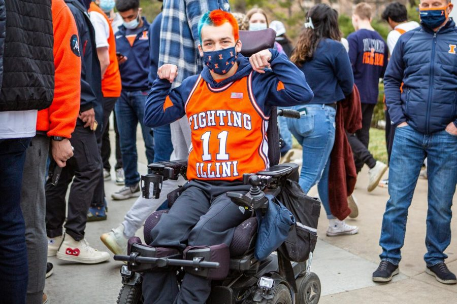 A student at the University poses in Illini gear after the Big Ten Championship. Masks will be required on campus until further notice since the University follows CDC protocol.