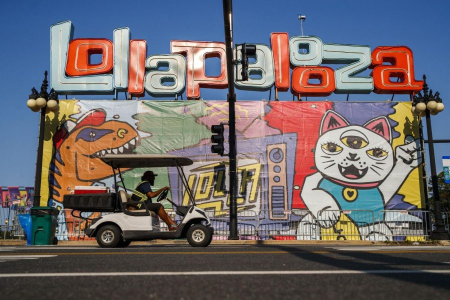 A golf cart drives past a Lollapalooza sign outside an entrance near East Ida B. Wells Drive and South Michigan Avenue on Tuesday in Chicago. The four-day festival starts Thursday after a year long hiatus.