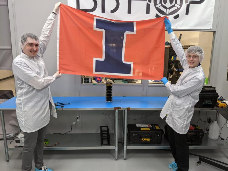 Undergraduate Aerospace Engineering students Rick Eason and Logan Power pose for a photo in front of their CubeSat satellite. The satellite will be loaded onto NASA's SpaceX Dragon cargo ship that will fly to the International Space Station.