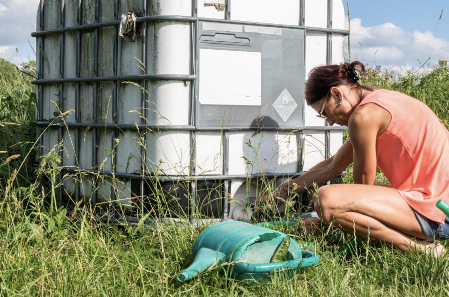 Rita Jasenauskas retrieves water for her garden in Alytus, Lithuania on June 28.