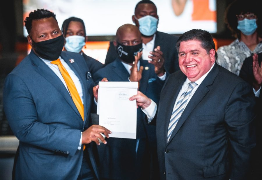 Rep. Kam Buckner and Gov. J.B. Pritzker pose with the newly enacted name, image and likeness bill at State Farm Center on Tuesday. Illinois student athletes will be able to profit off NIL starting Thursday.