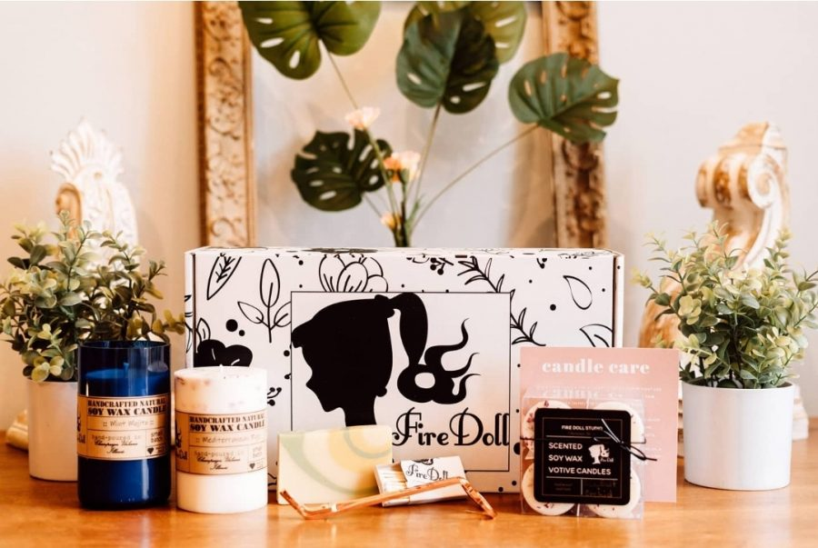 Merchandise from Fire Doll Studio is displayed on a table. The sustainable candle shop  will open in Downtown Champaign in August.