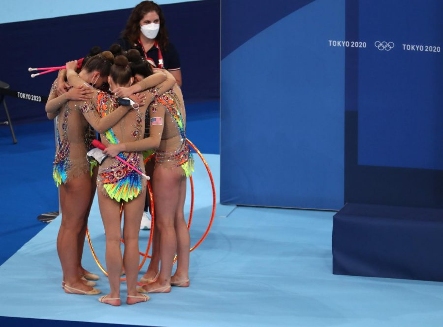 The U.S. rhythmic gymnastics team hug after completing their final routine on Saturday at the Ariake Gymnastics Center during the Tokyo Olympics. Columnist Nathaniel Langley argues that the Olympic host city displaces less affluent communities and expedites gentrification rather than uniting the world.