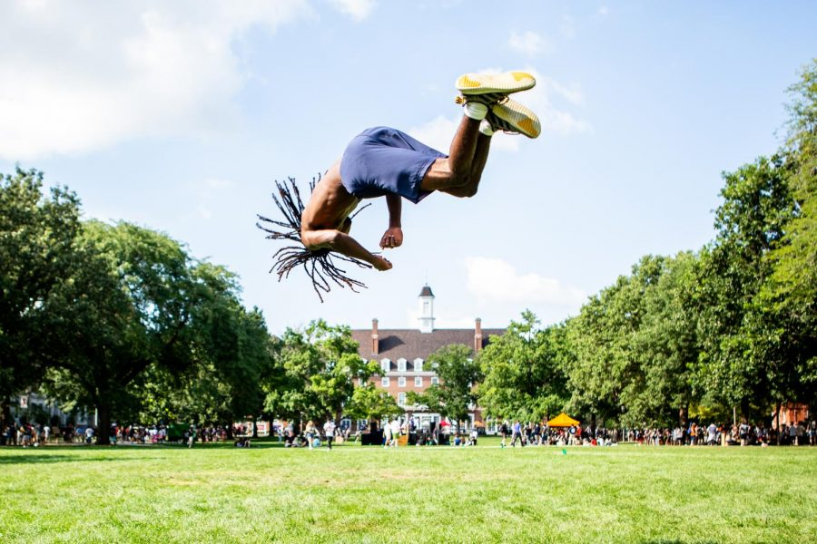 A member of the Illini Flyers twists through the air on the Main Quad during Quad Day on Aug. 22.