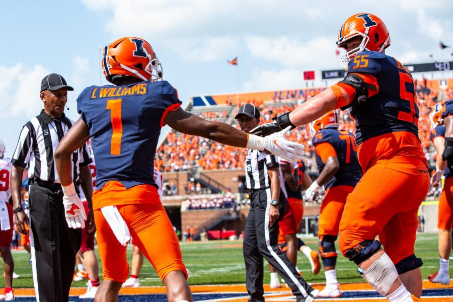 Isaiah Williams (1) high fives Blake Jeresaty (55) during the game against Nebraska at Memorial Stadium on Saturday. Williams and Deuce Spann both made position changes from quarterback to receiver this offseason and had immediate impacts against the Cornhuskers in the 30-22 Illini win.