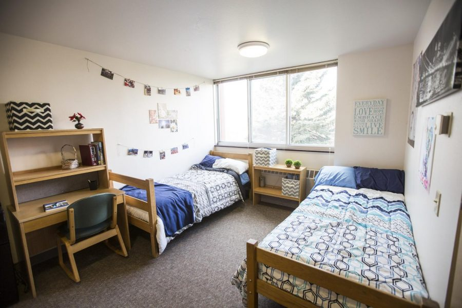 Two twin beds sit opposite each other in a dorm room with sunlight coming in through the window. Stick to habits while living in the dorms.