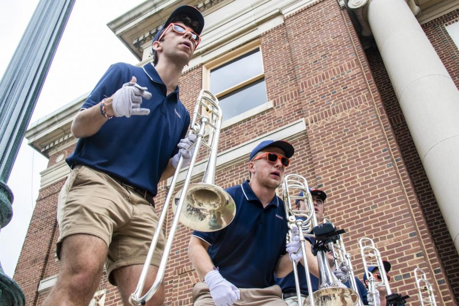 Members of the trombone section of the Marching Illini perform on the steps of Foellinger Auditorium during Quad Day on Aug. 22. The band has changed their routine and uniforms to aid in increased fan reactions at sporting events.