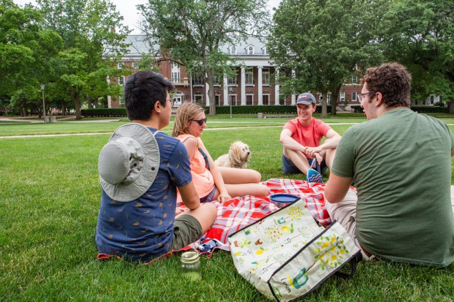 Music Education Major graduates Emmett O'Brien, Katie Mitchell, Ollie (dog), Marcus Moone, and Brendon Culloton, enjoy a picnic on the Main Quad. Spend the day exploring the campus to take a breather from your dorm room.