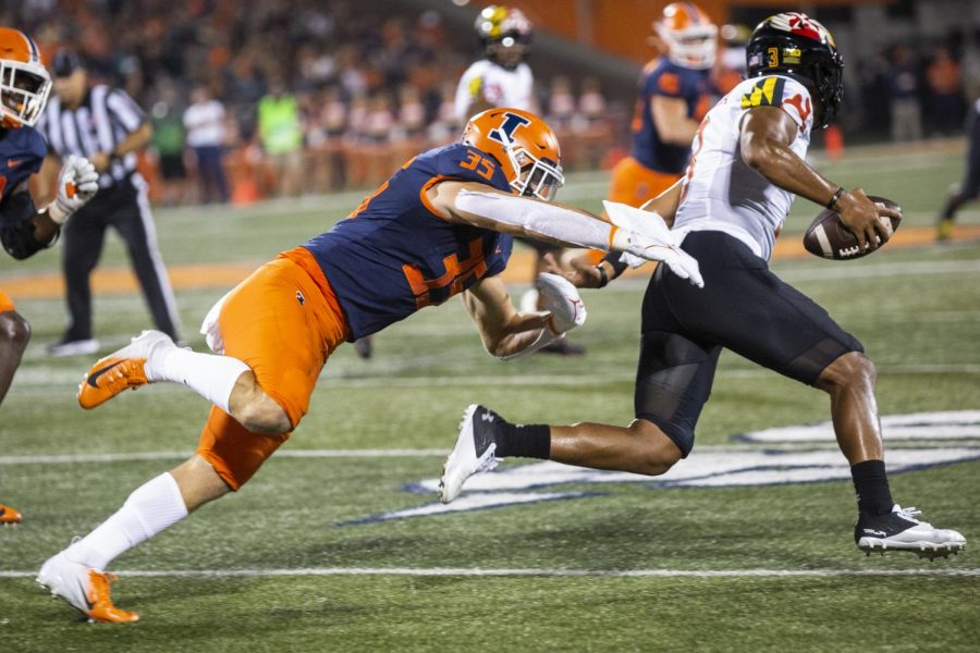 Illinois linebacker Jake Hansen tries to tackle Maryland quarterback Taulia Tagovailoa during the game between the Illini and the Terrapins on Sept. 17 at Memorial Stadium.