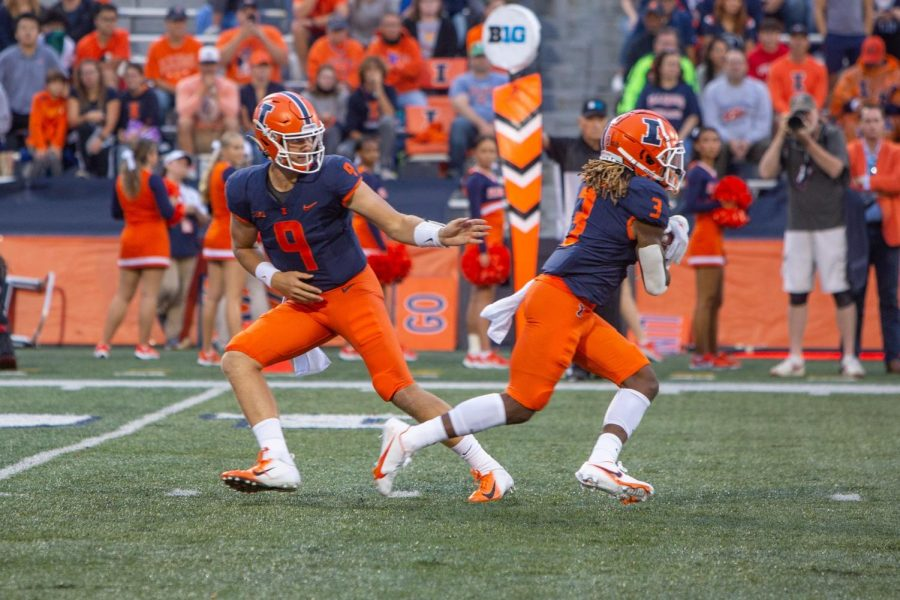Quarterback Artur Sitkowski hands the ball off to running back Jakari Norwood during the game against UTSA on Sept. 4. With uncertainty at the quarterback position, the Illini will need consistent production from their running backs.