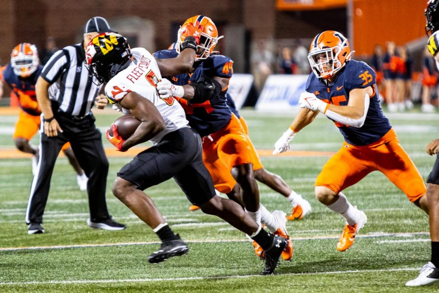 Offensive linebacker Seth Coleman and linebacker Jake Hansen tackle their Maryland opponent during the game at Memorial Stadium Sept. 17. The Daily Illini sports staff makes predictions ahead of the Illinis matchup with Charlotte.
