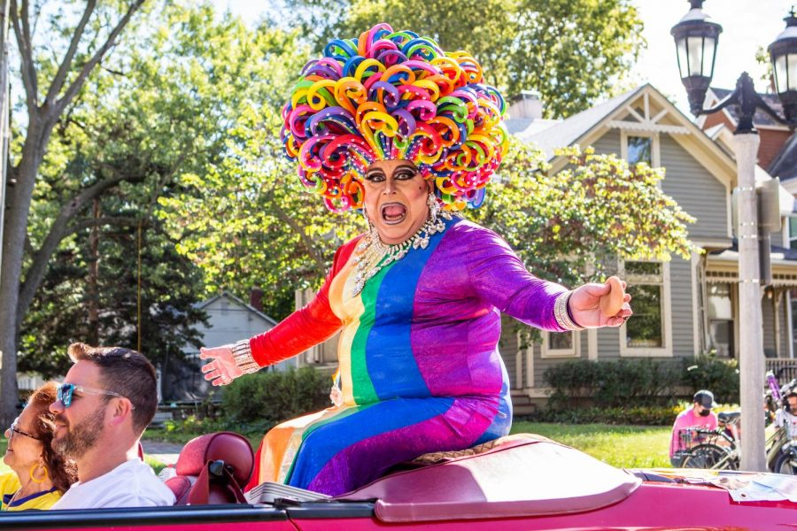 A drag queen in rainbow attire and a homemade pool noodle wig sits on top of a convertible at the C-U Pride Parade on Saturday. The parade uplifted the LGBTQ+ community.