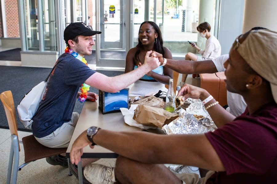 Students sit around talking at a table eating food at Ikenberry Hall. Dining halls are now returning to in person dining this semester.