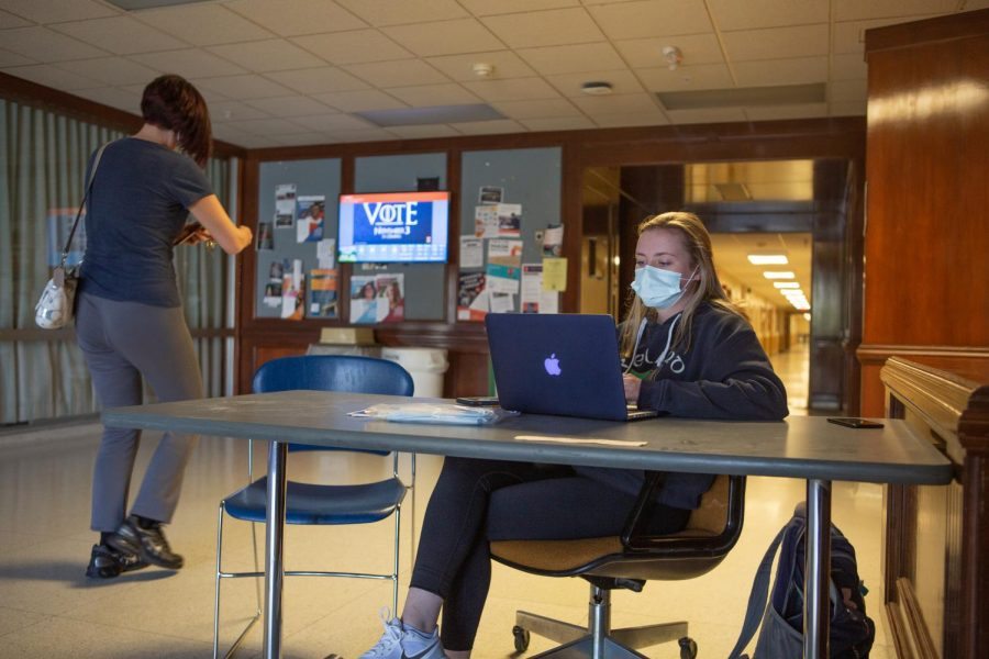A University Wellness Associate checks a woman into Bevier Hall on Oct. 15. The University has not hired enough Wellness Associates to be stationed at every building on campus, however, UI is still confident in their COVID-19 mitigation measures.