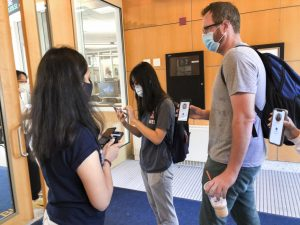 A University Wellness Associate checks two people into the Gies College of Business on Tuesday morning. The University has not hired enough Wellness Associates to be stationed at every building on campus, however, UI is still confident in their COVID-19 mitigation measures.