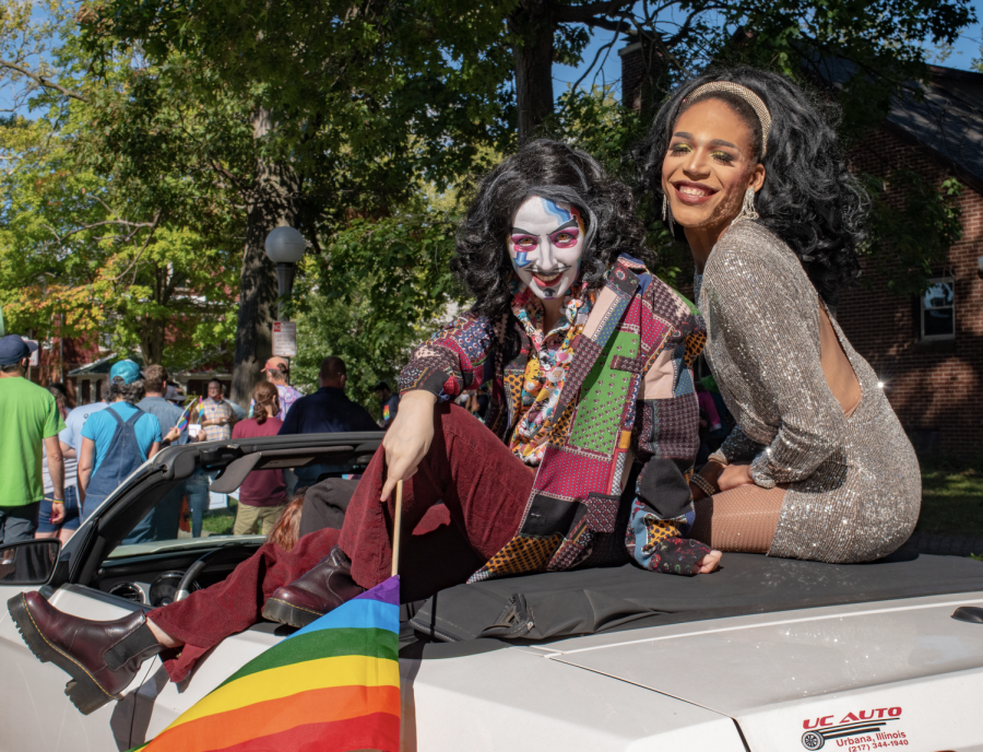 Two drag queens ride atop a white convertible during the CU Pride Parade on Saturday. The community rallied together in support of pride while honoring AIDS history.
